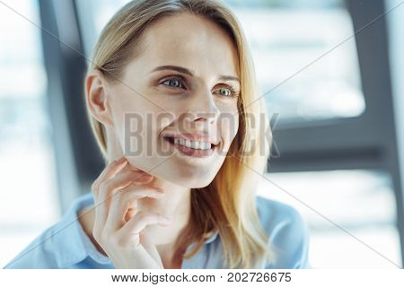 True visionary. The portrait of a charming young fair-haired woman looking at the distance with a dreamy look while touching her neck