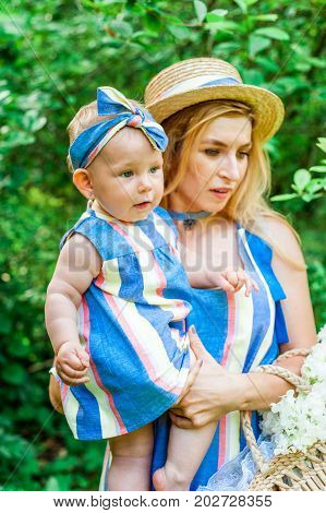 Woman in blue dress raises up her little daughter in the same clothes plaing with her