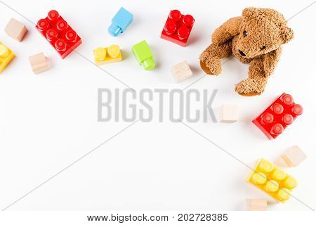 Kids toys background with teddy bear and colorful blocks. Top view