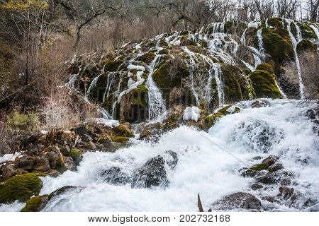Waterfall in the forest. Frozen water drains over the rocks. The rock is covered with moss on which cold water flows.Rock in moss. The rock in the moss on which the water flows down