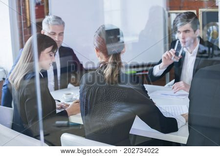 Business colleagues meeting in conference room, shot through glass