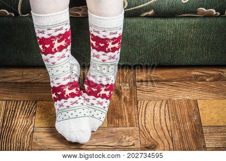 female legs in Christmas socks on the floor in the house. Festive decorations for Christmas