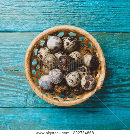 Image of quail eggs in straw basket on blue wooden table.