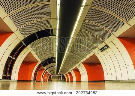 VIENNA - JUNE 1, 2016: Red corridor and white lights inside metro station of Vienna U-Bahn on June 1, 2016 in Austria. More than 1.3 million passengers use the Vienna U-Bahn every day