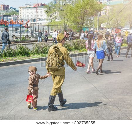 the child in the form of military parade, with parents. celebration of the victory day parade on May 9, the year 2017. Vladivostok, Russia. on a sunny day