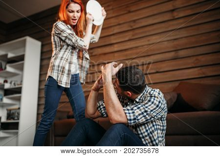 Angry woman breaking dishes, family quarrel