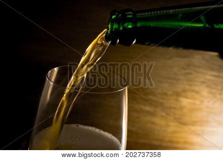 Champagne pouring into a wine glassWhite wine from wine bottleFocus glass and white wine