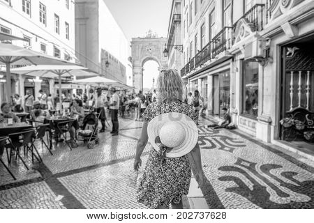 Tourism in Europe. Woman walking on popular Rua Augusta between cafes and shops in Baixa, downtown of Lisbon, Portugal. Triumphal Arch and King Dom Jose I on defocused background. Black and white shot
