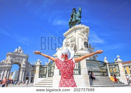 Happy woman with open arms in front of King Dom Jose I equestrian statues in Praca do Comercio or Commerce Square with Triumphal Arch. Female tourist enjoying in Lisbon, Baixa District in a sunny day.