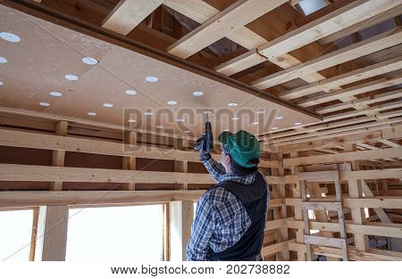 Construction worker thermally insulating eco wooden frame house with wood fiber plates