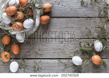 Poultry farm concept. Fresh brown and white eggs with hay on linen textile at rustic wood background with copy space. Top view. Rural still life, natural organic healthy food.