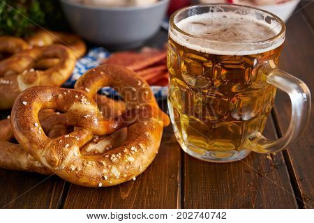 Traditional munich pretzel next to mug of beer on wooden tabele for Oktoberfest. Close up.