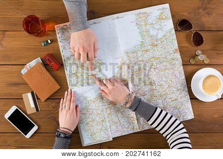 Couple planning trip to London, England, pointing on this city on map. Travel background with accessories