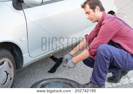 Man Changing A Flat Tire On The Side Of The Road
