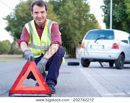 Man Putting Danger Triangle Sign After Car Breakdown