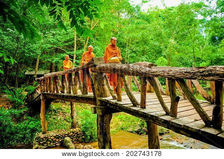 Kanchanaburi Thailand - July 14 2012: Buddhist monks marching on wooden bridge to seek alms in morning. This is usual every day duty of Buddhist monks.