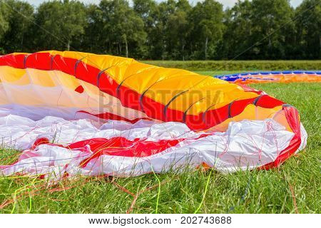 Parachute of paraglider lying in green meadow