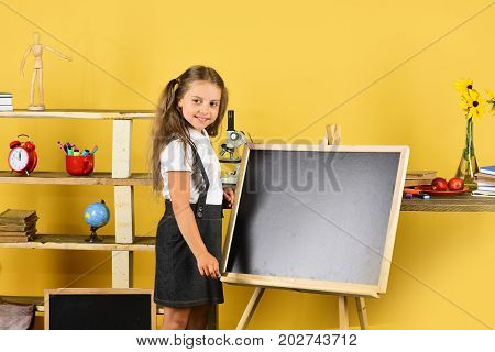 Schoolgirl With Smiling Face Near Bookshelf With School Items