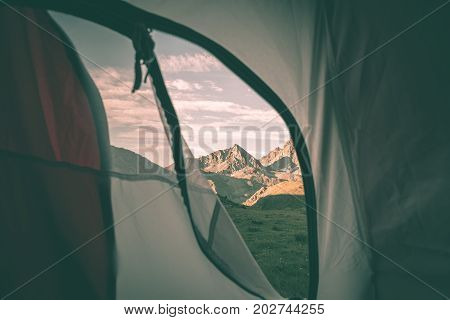 Looking Out The Mountain Landscape At Sunrise From Interior Of Camping Tent. Adventure Traveling On