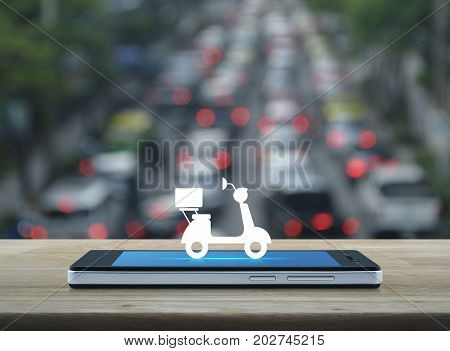 Motor bike icon on modern smart phone screen on wooden table over blur of rush hour with cars and road Business delivery service concept