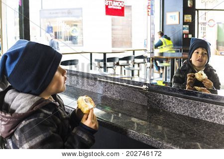 Adorable boy eating sweet donut and looking at mirror in a coffee shop on a cold morning in London