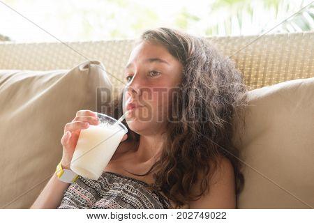 Portrait of beautiful young woman enjoying a drink pretty girl sipping banana juice in coffee shop terrace