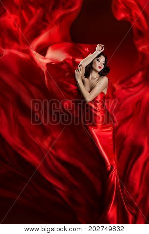 Fashion Model Art Dress Woman Dancing in Red Waving Fabric Beautiful Girl on Artistic Cloth background
