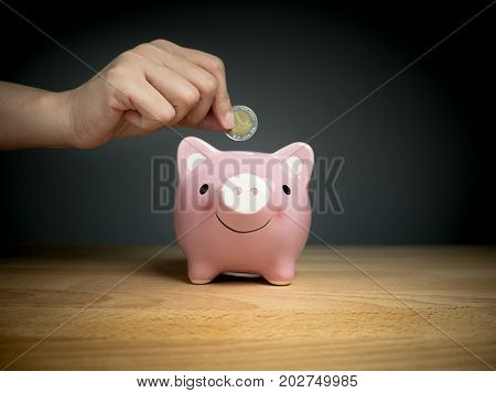 hand add coin to piggy bank save coin time and money concept.