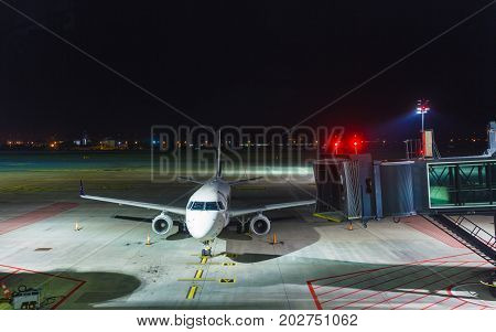 Travel transport aircraft concept. Big white passenger jet plane on runway at the airport night.