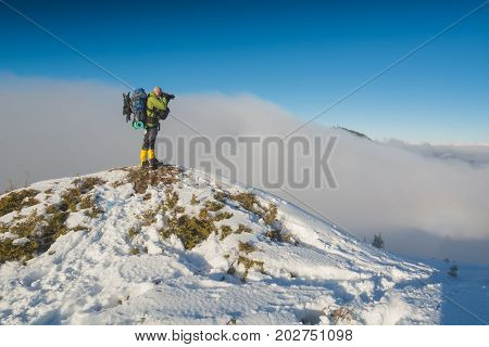 Photographer with a camera taking photos of beautiful winter foggy mountain valley. Carpathians Ukraine Europe.