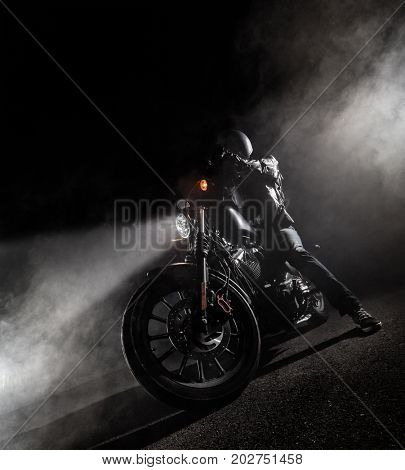 High power motorcycle chopper at night. Smoke effect on dark background.