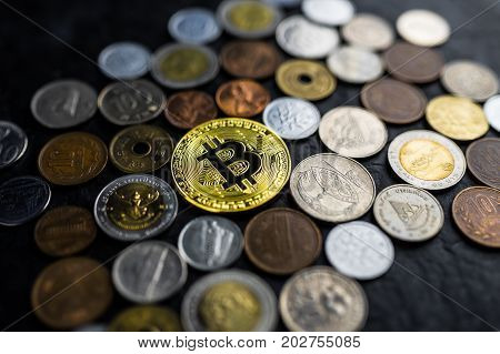 Golden bitcoin with international money coins new currency among old currencies business and finance concept on black stone table background selective focus