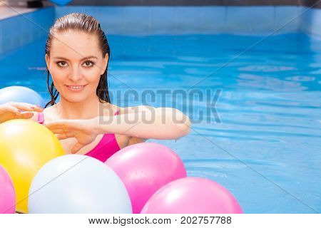 Relax spa hotel wellness concept. Woman having fun with balloons in water. Pretty girl relaxing at swimming pool.