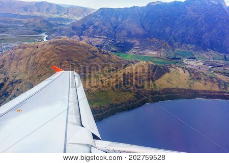 Scenery from airplane 's window after taking off seeing wing of airplane and landscape of Queenstown South Island of New Zealand