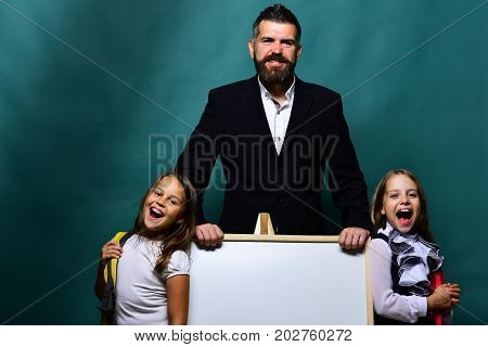 Girls and man with happy faces. Kids wearing schoolbags stand next to whiteboard and bearded teacher copy space. Schoolgirls near marker board and guy on dark cyan background. Back to school concept