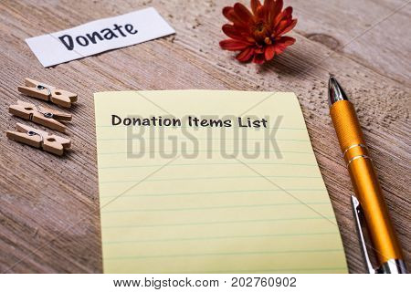 Donation Items List concept on notebook and wooden board