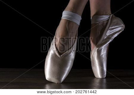 Feet of ballerina in Pointe shoes champagne color on the wooden floor. Hard bright light. Closeup on a black background.