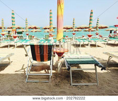 Italian beach with umbrellas and deck chair