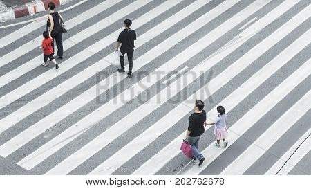 Crowd of people and group of family with child walk on street pedestrian crossroad in the city street from top view bird eye view.