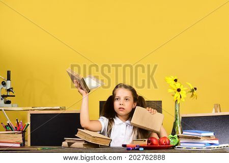 Schoolgirl With Puzzled Face Holds Books. Kid And School Supplies