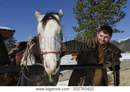 Young man caressing horse infront of a horse barn