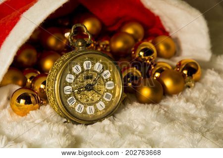 Gold alarm clock with gold Christmas balls under the Santa's hat. Christmas atmosphere. Christmas rush.