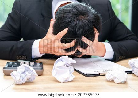 Stressed businessman make a mistake with chewed paper - migraine or headache concept