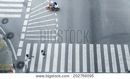 Crowd of people walk on street pedestrian crossroad in the city street with the motorcycle drives pass road from top view bird eye view.