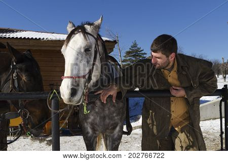 Young man with chaps and two horses infront of barn. Selective focus