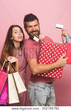 Guy with beard and pretty lady do shopping. Couple in love hugs holding big box and shopping bags on pink background. Man with smiling face holds credit cards. Shopping and money spending concept