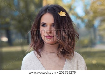 Perfect Woman with Yellow Autumn Leaf in Brown Hair Outdoors. Beautiful Model in Autumn Park