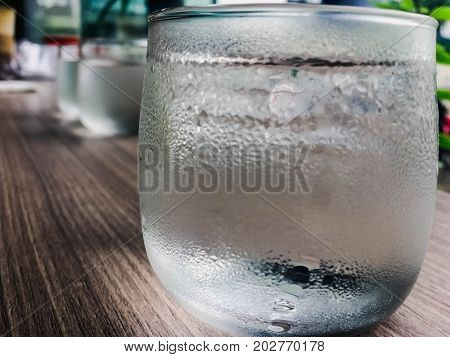 Closeup and burry glass of water on table