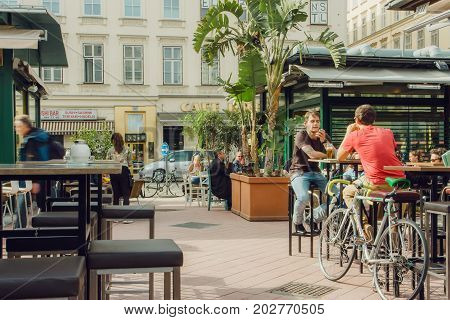 VIENNA, AUSTRIA - JUN 6, 2013: Young people meeting and drinking in popular outdoor city bar with tall tables on June 6, 2013. Vienna city has population near 1.8 million