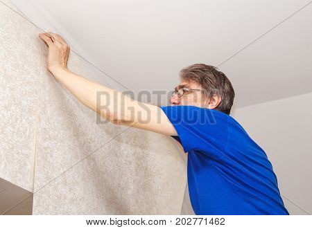elderly worker attaching wallpaper on the wall in his house